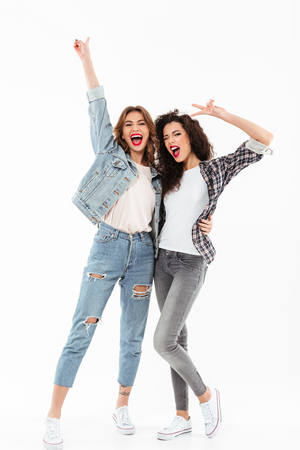 Full length image of two joyful girls standing together and showing peace gestures while looking at the camera over white background Stock Photo