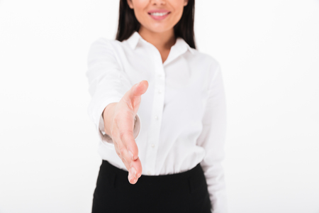Close up of a friendly asian businesswoman greeting you with outsretched hand isolated over white background