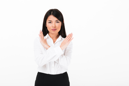 Portrait of a serious asian businesswoman showing stop gesture with crossed hands isolated over white background