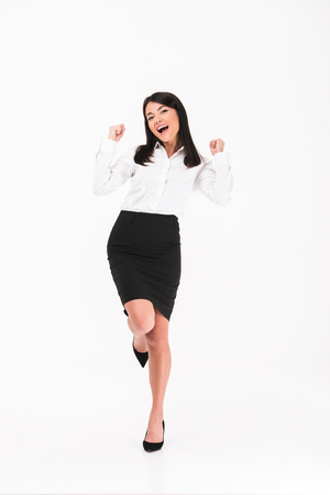 Full length portrait of a cheerful asian businesswoman standing and celebrating success isolated over white background Stock Photo