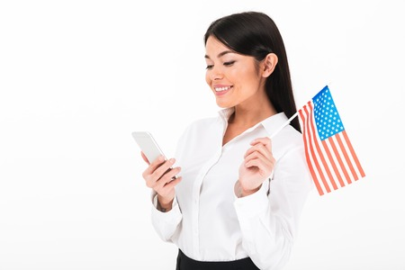 Portrait of a satisfied asian businesswoman holding american flag while standing and using mobile phone isolated over white background Stock Photo