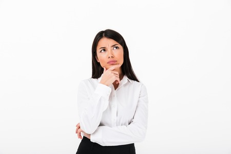 Portrait of a pensive asian businesswoman thinking and looking away at copy space isolated over white background
