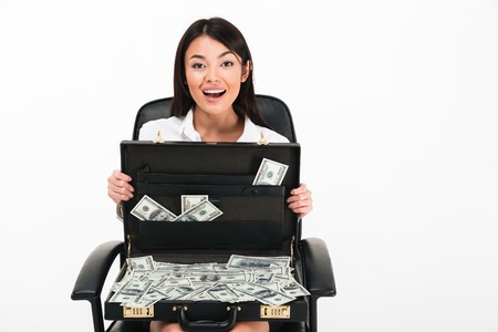 Portrait of an excited asian businesswoman holding open briefcase full of money banknotes while sitting in an office chair isolated over white background
