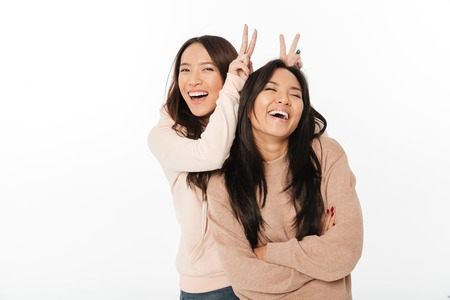 Picture of two asian cute ladies sisters standing isolated over white background looking camera have fun.