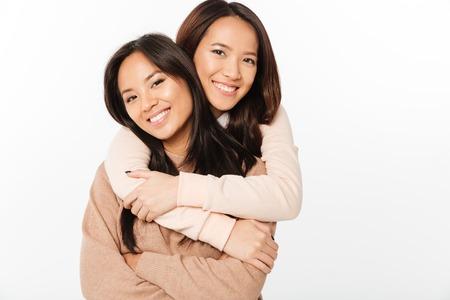 Beeld van twee Aziatische vrij vrolijke dameszusters die met elkaar koesteren. Zoek camera.