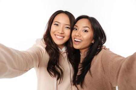 Het beeld van twee Aziatische gelukkige positieve dameszusters maakt selfie kijkend camera.