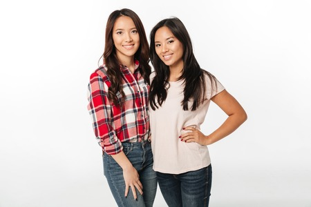 Image of two asian pretty cheerful ladies sisters hugging with each other. Looking camera.