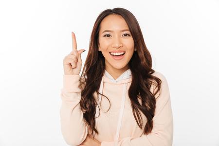Het beeld van Aziatische positieve dame status geïsoleerd over witte achtergrond die camera kijken heeft een idee. Stockfoto