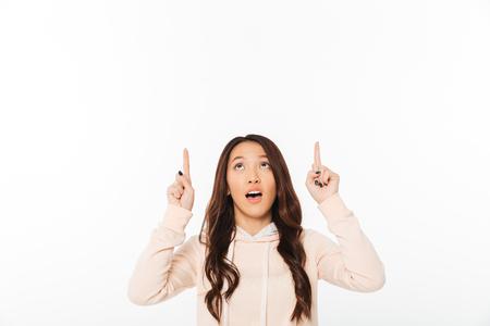 Foto van Aziatische leuke dame status geïsoleerd over witte achtergrond die opzij richt kijkend.