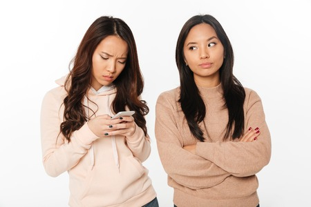 Photo of asian girl displeased because of her sister chatting by mobile phone. Looking aside.