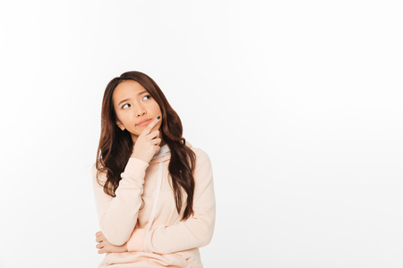 Image of asian thinking lady standing isolated over white background looking aside.