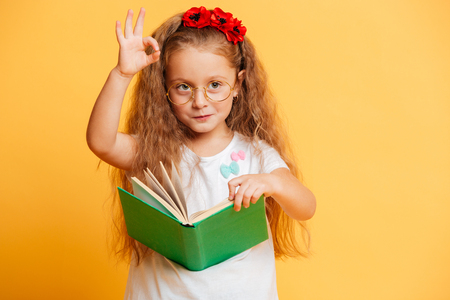 Image of little cute pretty girl standing isolated over yellow background wearing glasses looking aside reading book showing okay gesture.