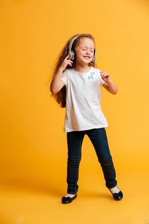 Photo of little girl dancing isolated over yellow background listening music with headphones. Eyes closed. 版權商用圖片
