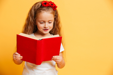 Image of little pretty cute girl standing isolated over yellow background reading book looking aside.