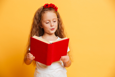 Picture of concentrated little pretty girl standing isolated over yellow background reading book looking aside.