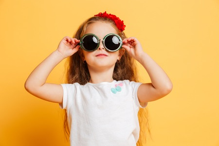 Photo of little cute serious pretty girl standing isolated over yellow background wearing sunglasses looking camera.