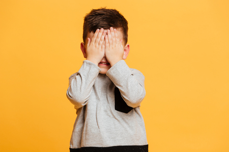 Image of little boy child standing isolated over yellow background covering eyes with hands. Stock Photo