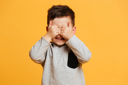 Picture of smiling cute little boy child standing isolated over yellow background showing thumbs up covering eyes.
