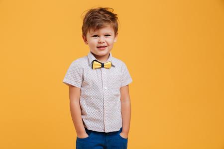 행복 한 작은 소년 아이 서의 이미지는 노란색 배경 위에 절연. 옆으로 봐. 스톡 콘텐츠