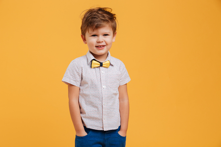 Image of happy little boy child standing isolated over yellow background. Looking aside.