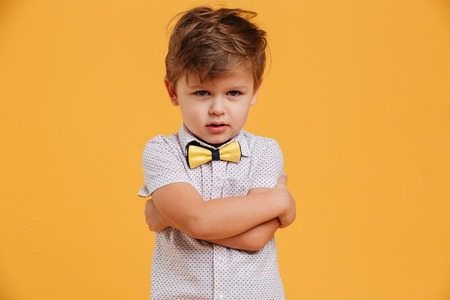 Portrait of a sad little boy child standing isolated over yellow background. Looking aside.