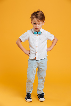 Image of angry little boy child standing isolated over yellow background. Looking camera. Stock Photo