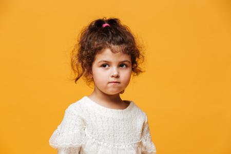 귀여운 작은 소녀 자식 서 격리 된 노란색 배경 위에 사진. 옆으로보고.