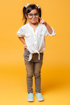 Image of cheerful little girl child wearing glasses standing isolated over yellow background pointing to you. Stock Photo