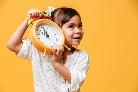 Photo of cheerful little girl child standing isolated over yellow background holding clock alarm.