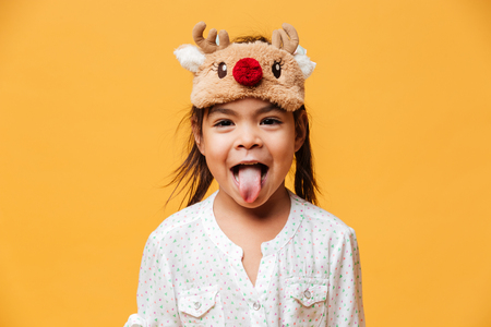 Photo of smiling little girl child standing isolated over yellow background wearing christmas cute mask showing tongue. Stock Photo