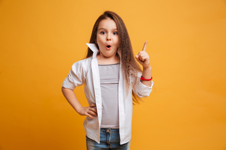 Image of surprised little girl child standing isolated over yellow background have an idea.