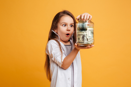 Photo of shocked little girl child standing isolated over yellow background holding jar with money. Archivio Fotografico