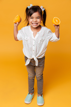 Photo of little girl child standing isolated over yellow background holding orange.
