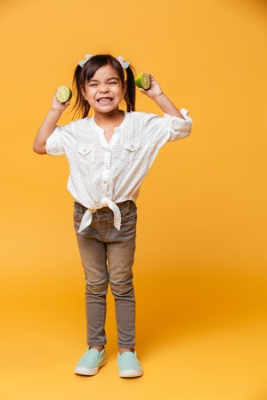 Photo of little girl child standing isolated over yellow background holding lime.