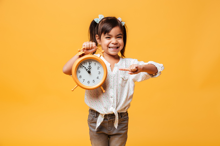 Photo of smiling little girl child standing isolated over yellow background holding clock alarm.