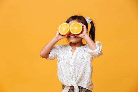 Photo of little girl child standing isolated over yellow background. Covering eyes with orange.
