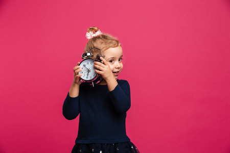 Intrigued young blonde girl holding alarm clock in studio over pink background