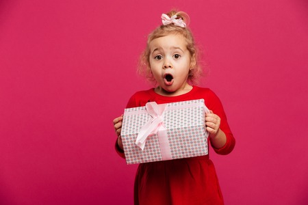 Shocked young blonde girl in red dress holding gift box and looking at the camera over pink background Stockfoto
