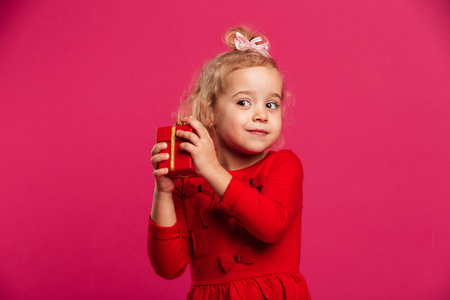 Intrigued young blonde girl in red dress holding gift box and looking aside over pink background Stock Photo