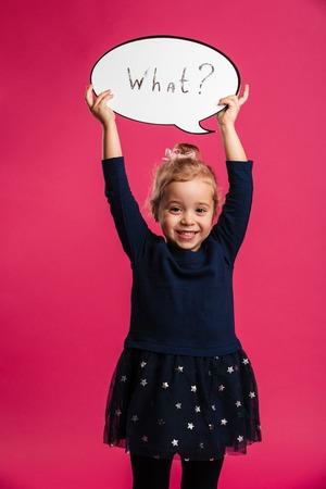 Verticaal beeld van Gelukkige jonge blonde meisjesholding toespraakbel wat en bekijkend de camera over roze achtergrond