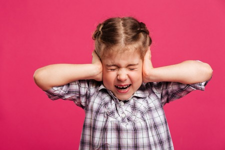 Image of screaming emotional little girl child standing isolated over pink background holding head with hands.