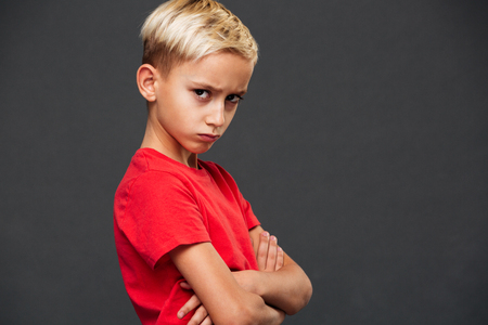 Photo of angry little boy child standing isolated over grey background. Looking camera with arms crossed. Archivio Fotografico