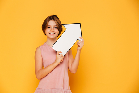 Cheerful handsome girl in pink dress holding arrow up at copy space and looking camera isolated over yellow Stock Photo