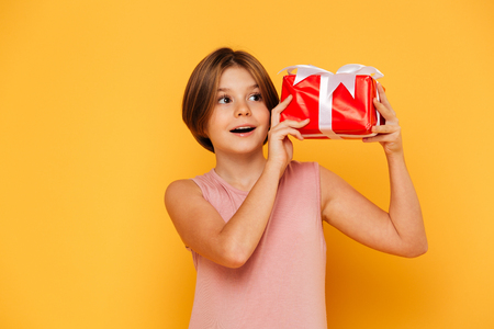 Portrait of little happy girl holding gift and looking aside isolated oer yellow
