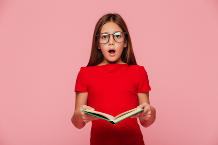 Surprised brunette girl nerd in eyeglasses looking camera with opened mouth while reading book isolated