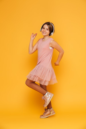Funny smiling girl in dress listening music in headphones and dancing isolated over yellow