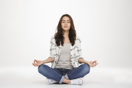 Full-length picture of concentrated woman in casual clothes meditating with closed eyes while sitting in lotus pose on the floor isolated over white wall Foto de archivo