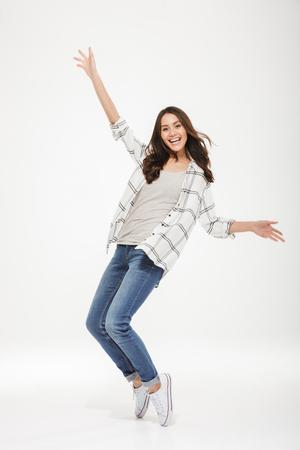 imagen integral de la mujer morena feliz en camisa divirtiéndose y mirando a la cámara sobre fondo gris