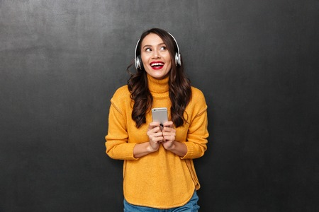 Happy brunette woman in sweater and headphones listening music by smartphone while looking up over black background Imagens