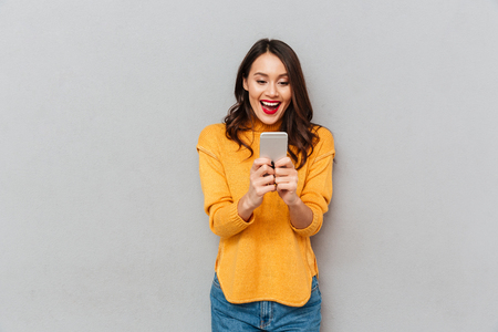 Image of Surprised happy brunette woman in sweater using smartphone over gray background